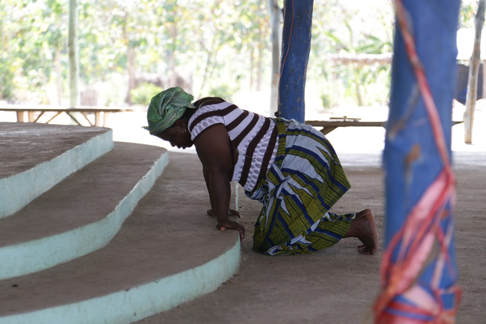 A woman kneels at a prayer centre a few miles away from Paul Noumonvi's.